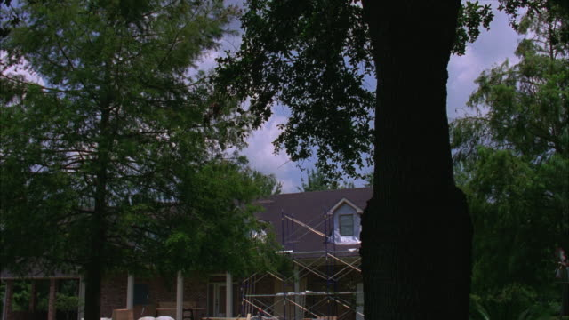 pan right to left of middle class house with dormer windows and small columns on front porch. ladders and construction materials in front yard indicate house under renovation. trees in large front yard. - dormer stock videos and b-roll footage
