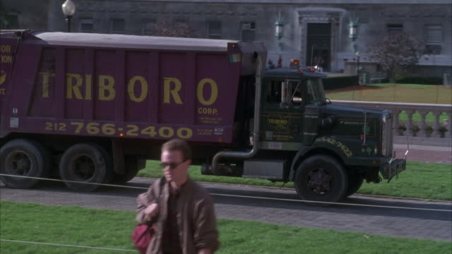 TRACKING SHOT OF GARBAGE TRUCK THAT READS TRIBORO DRIVING LEFT TO RIGHT ON CAMPUS AT COLUMBIA UNIVERSITY. STUDENTS WALK AROUND.