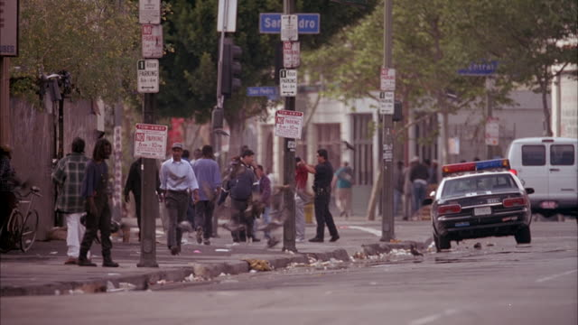 medium angle of sidewalk, sign above reads san dro for san pedro street. police car parked next to sidewalk, two police place handcuffs on man. view obscured by passing traffic. - anno 1999 video stock e b–roll