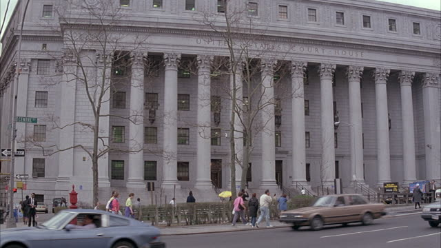 medium angle of new york city courthouse with corinthian columns and engraving above that reads united states court house. cars drive by from right to left on street. - korinthisch stock-videos und b-roll-filmmaterial
