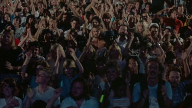 medium angle of cheering crowd at rock concert. pans back and forth of different parts of crowd. see crowd clapping, waving arms, dancing to music. primarily young crowd. red light reflects off crowd. could be from stage lights. - dancing back to back stock videos & royalty-free footage