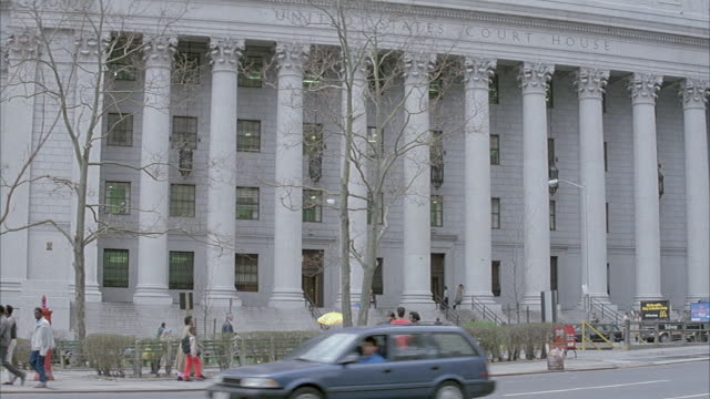 medium angle of new york city courthouse with corinthian columns and engraving above that reads united states court house. people walk around in front of building. - korinthisch stock-videos und b-roll-filmmaterial