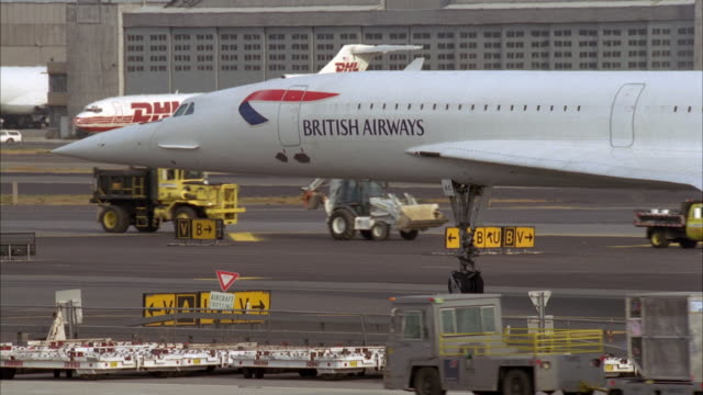 medium angle of front end of british airways concorde on runway at airport. dhl airplane and hangar in background. airport vehicles drive by on runway. - british aerospace concorde stock videos & royalty-free footage