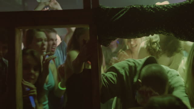 medium angle of crowd of party / rave goers escaping through window. partiers are young adults, college aged. some wear glow necklaces. they are running, screaming and panicking. - terrified stock videos & royalty-free footage