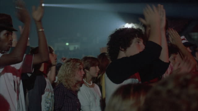 HAND HELD CLOSE UP SHOT OF A ROCK CONCERT AUDIENCE (YOUNG AND DRESSED IN EARLY 1980'S ATTIRE) THE CROWD IS SEEN WITH ARMS RAISED, CLAPPING AND PUMPING THE AIR, AS THEY DANCE TO THE MUSIC.