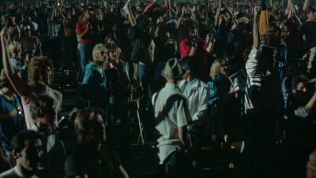 PAN R-L ON CROWD OF PEOPLE ATTENDING ROCK CONCERT, REVEALING AN ARRAY OF PEOPLE CLAPPING HANDS AND WAVING THEM IN THE AIR. CAMERA CONTINUES PANNING L-R AND R-L SEVERAL TIMES. AUDIENCE IS RELATIVELY YOUNG AND DRESSED IN EARLY 1980'S ATTIRE.