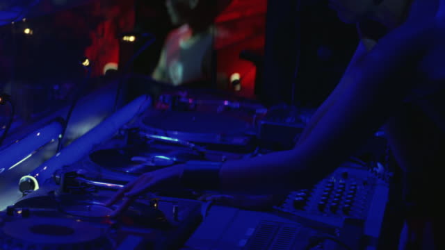 MEDIUM ANGLE OF DISC JOCKEYS PLAYING MUSIC ON TURNTABLES IN NIGHT CLUB. CAMERA PANS UP TO SEE DISC JOCKEYS PLAYING AND SCRATCHING RECORDS ON TURNTABLES. SEE PEOPLE DANCING IN BACKGROUND.