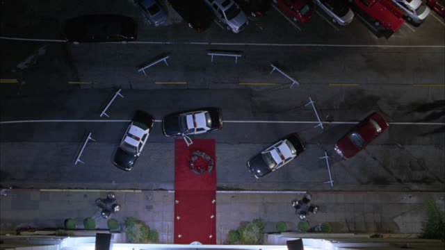 vídeos de stock, filmes e b-roll de high angle down of police cars parked in front of hotel red carpet entrance. police officers in huddle on carpet disperse and return to cars. - estreia