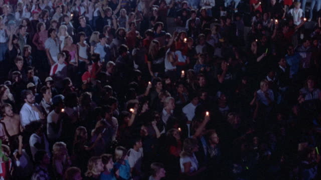 YOUNG ROCK CONCERT AUDIENCE IN EARLY 1980'S ATTIRE. CROWD HAS ARMS IN THE AIR, CLAPPING AND DANCING WITH SOME HOLDING LIGHTERS IN THE AIR. PAN OVER THE AUDIENCE, PAUSING OCCASIONALLY.