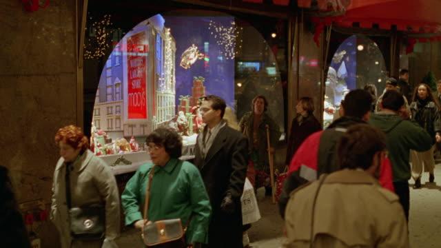 vídeos y material grabado en eventos de stock de medium angle of storefront window displays of macy's department store of christmas decorations. pedestrians walk by on sidewalk. - macy's