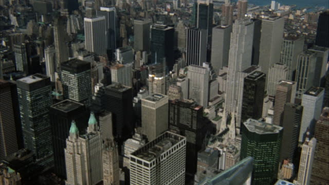 aerial. moving shot of downtown new york city. pans r-l of  manhattan skyscrapers and high rise buildings. see empire state building. harlem river in bg. - manhattan stock videos & royalty-free footage