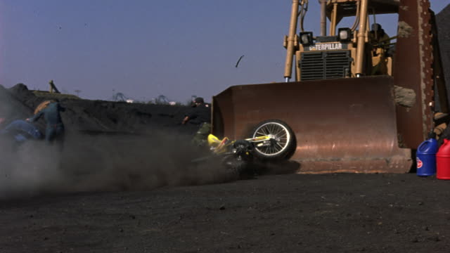 MEDIUM ANGLE OF MOTORCYCLE STUNT. SEE BIKER ON DIRT BIKE MOUNTED MIDAIR. BYSTANDERS WATCHING. BIKE IS SHOT OUT LIKE A CANNON. PANS LEFT TO RIGHT. BIKE CRASHES INTO TRACTOR AND BIKER FALLS OFF OF BIKE.