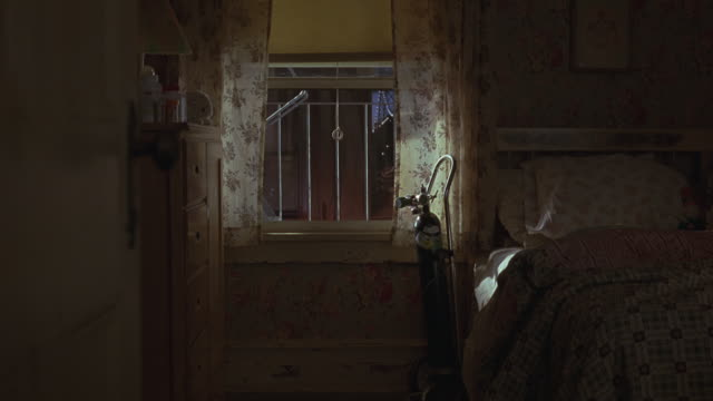 medium angle looking through new york apartment bedroom window. see fire escape and neighboring apartment buildings. see child's, possibly girl's, bed and drawers. see oxygen tank next to window's curtains. - fire escape stock videos and b-roll footage