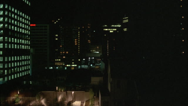 vídeos de stock e filmes b-roll de pan up. camera appears to be looking out from inside of elevator. elevator moving up. see park and courtyard of building. high rise office building in foreground and background. shot pans up to top of buildings. see city skyline in background. - elevador