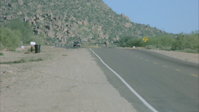 TRACKING SHOT OF EARLY 1980'S BROWN CHRYSLER LEBARON DRIVING DOWN DESERT ROAD. SEE DESERT CACTUSES AND TREES. MOUNTAINS IN DISTANCE.