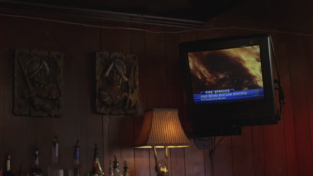 vídeos de stock, filmes e b-roll de hand held of fire action playback on television screen attached to wall. firefighters on screen. could be news item. alcohol bottles visible next to television. could be motel room or bar. - 1980 1989