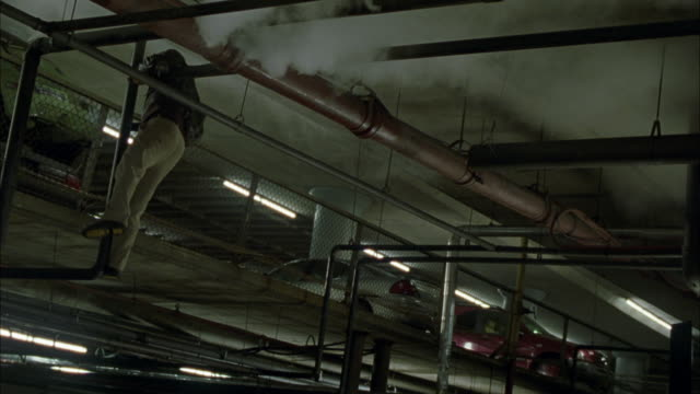 MEDIUM ANGLE OF MAN HANGING FROM METAL PIPE NEAR CEILING OF WAREHOUSE OR CONCRETE BUILDING. MAN HOLDS GUN AND FALLS DOWN, OUT OF FRAME. AN EXPLOSION OF SPARKS ILLUMINATES THE FRAME, AND SMOKE EMERGES FROM ABOVE. STUNTS
