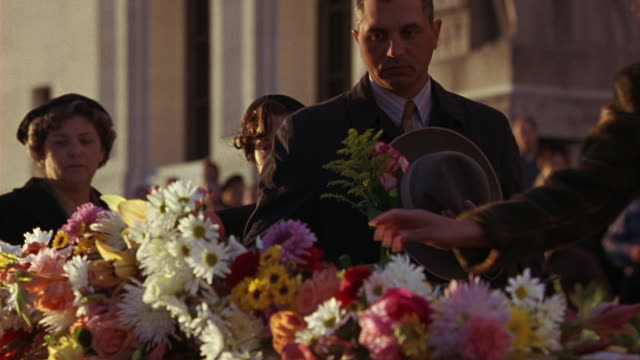 medium angle of line of mourners walking past casket, placing flowers, paying respects. crowd includes men, women, children of all walks in front of louisiana state capitol building. - kapitol von louisiana stock-videos und b-roll-filmmaterial