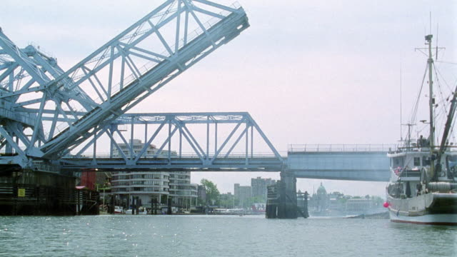 wide angle of two drawbridges in port area. see one drawbridge lifted up while large fishing boat passes through. see cars driving down bridge behind. - drawbridge stock videos and b-roll footage