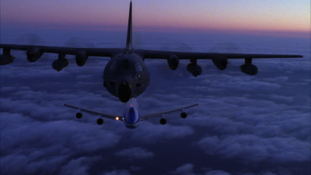 MEDIUM ANGLE OF AIR FORCE ONE JET AND C-130 HERCULES AIRPLANE FLYING TOWARD CAMERA ABOVE CLOUD COVER.