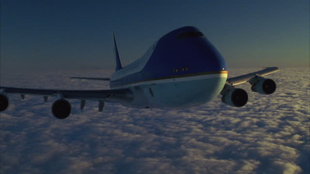 MEDIUM 3/4 FRONT ANGLE OF AIR FORCE ONE FLYING OVER LAYER OF WHITE CLOUDS IN SKY. AIRPLANE PULLS UP AND EXIT FRAME TO TOP. SEE HORIZON OF CLOUDS AND BLUE SKY.
