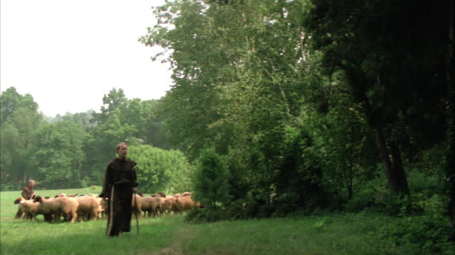 medium angle of monks and sheep. camera pans across forest and rests on view of monastery or church or convent through trees. - monk stock videos & royalty-free footage