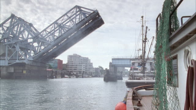 wide angle or harbor with drawbridge lifted at left. see partially blocked boat at right. see two boats in water. see a building in the background. sky is overcast and gray. - drawbridge stock videos and b-roll footage