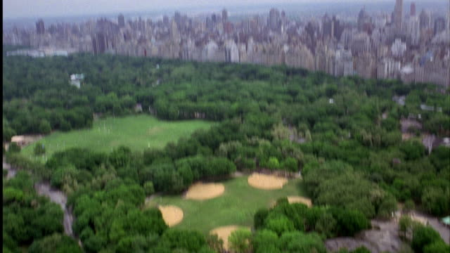 aerial birdseye pov. camera mounted on track. camera move along track to edge of high rise. camera falls down side of building. stops midway. looking down on city street. pans up to central park. overcast weather. - anno 2001 video stock e b–roll