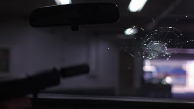 close angle of right hand holding hand gun or pistol with silencer. see lit parking garage from pov inside car driving. - schusswaffe stock-videos und b-roll-filmmaterial
