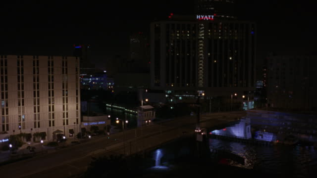 stockvideo's en b-roll-footage met medium angle high rise hyatt hotel, see multi-story white bank building to left, overpass with water underneath. see cars move on overpass. see other high rise buildings and city lights in background. - hyatt