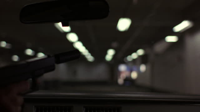 close angle of right hand holding hand gun or pistol with silencer. see lit parking garage from pov inside car. see partial dashboard with air vents at bottom. see hand shake as it points gun to right. - schusswaffe stock-videos und b-roll-filmmaterial