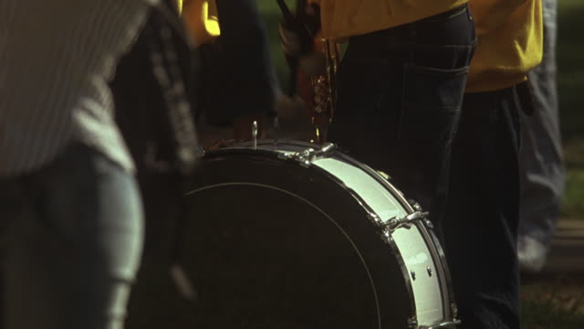 medium angle of crowd, people, students.  could be college campus, high school. young man with marching band drum kit at his feet. - marching band stock videos and b-roll footage
