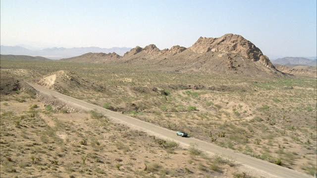 WIDE ANGLE OF DESERT HIGHWAY WITH BLUE JEEP HEADING LEFT. SEE SHRUBS AND SOME MOUNTAINS BY ROAD.