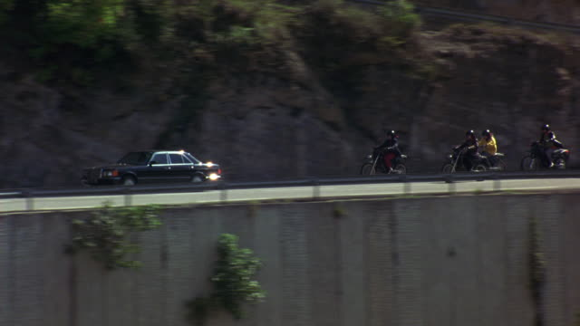 wide angle of mountain road. camera pans right to left following motorcycles and mercedes benz s-klasse car driving over bridge. houses with tile roofs. could be motorcycle gang. - mercedes benz stock videos and b-roll footage