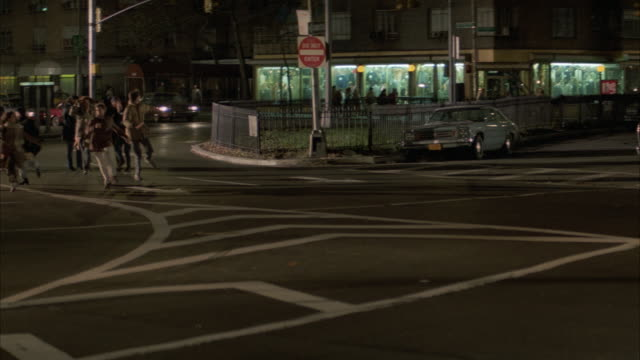 wide angle of new york city street, intersection. several cars drive toward camera and off screen to left. large mob or crowd of people enters and runs across exits screen from right to left. panic. - mob stock-videos und b-roll-filmmaterial