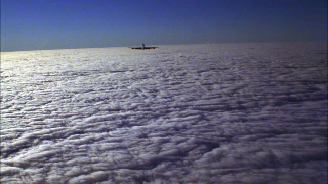 MEDIUM ANGLE OF AIR FORCE ONE JET FLYING ABOVE CLOUD COVER AWAY FROM CAMERA.