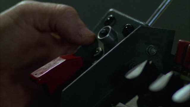 CLOSE ANGLE OF SWITCHES AND BUTTONS ON MILITARY EQUIPMENT, POSSIBLY ROCKET LAUNCHER, BOMB DETONATOR OR OTHER DEVICE. SEE LEFT HAND ON LEFT OF DEVICE. HAND PRESSES BUTTON ON TOP. SEE TWO RED LIGHTS FLASH.
