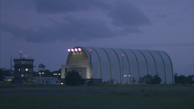 medium angle of airport runway. see control tower and airplane hangar next to runway. could be airport garage. see small buildings or trailers next to control tower. lights on in control tower. - airplane hangar stock videos & royalty-free footage