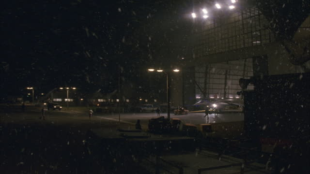 vídeos de stock e filmes b-roll de medium angle of empty lot outside of airplane hangar at night. see men walking around. see snow falling from dark sky. see bright lights. hangar door opens and military jet is pulled into view. - hangar