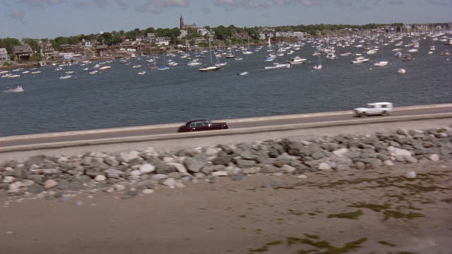 aerial tracking shot of rolls royce limousine driving on highway between two lakes, hundreds of boats on lake in background. drives into small town. - rolls royce stock videos and b-roll footage