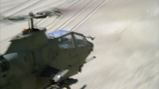 TRACKING SHOT OF COBRA MILITARY HELICOPTER FLYING ALONG DESERT OR BEACH, CAMERA PANS ALONG SIDE OF HELICOPTER. MIDDLE EAST. ATTACK HELICOPTERS.