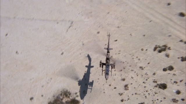 AERIAL BIRDSEYE POV OF COBRA HELICOPTER FLYING LOW TO LEFT. DESERT WITH SHRUBS ON GROUND. MIDDLE EAST. ATTACK HELICOPTERS.