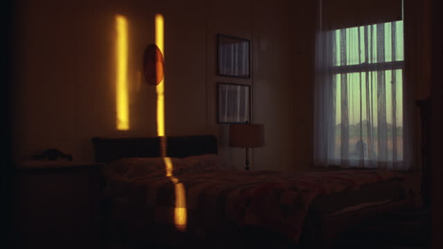 vídeos de stock, filmes e b-roll de wide angle of home interior of a bedroom, maybe a hotel or motel.  a ray of yellow light on the wall and across the bed.  wood bed frame, lamp, dresser, framed photos, a window covered with see through drapes. - quarto de dormir
