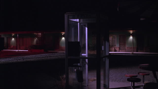 medium angle of telephone booth in front of small lower class motel. phone booth is next to plastic picnic table area in gravel parking lot. - 電話ボックス点の映像素材/bロール