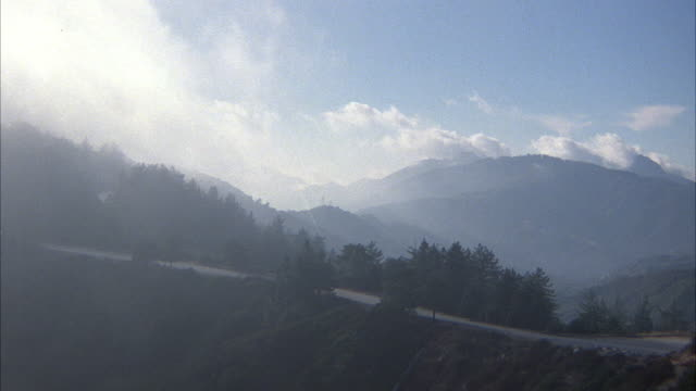 WIDE ANGLE OF CLOUDY OR FOGGY MOUNTAIN RANGE WITH EVERGREEN FORESTS. SEE MOUNTAIN ROAD DOWN HILL LEFT TO RIGHT. TRUCK ON ROAD APPEARS IN DISTANCE FROM LEFT. SHOT ROTATES COUNTER CLOCKWISE , ZOOMS IN ON ROAD AND TRUCK MOVES RIGHT TO LEFT.