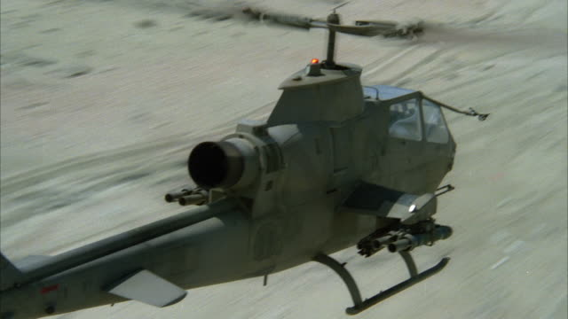 TRACKING SHOT OF COBRA MILITARY HELICOPTER FLYING ALONG DESERT OR BEACH, CAMERA PANS ALONG SIDE OF HELICOPTER AND MAKES BANKED RIGHT TURN AT END. MIDDLE EAST. ATTACK HELICOPTERS.