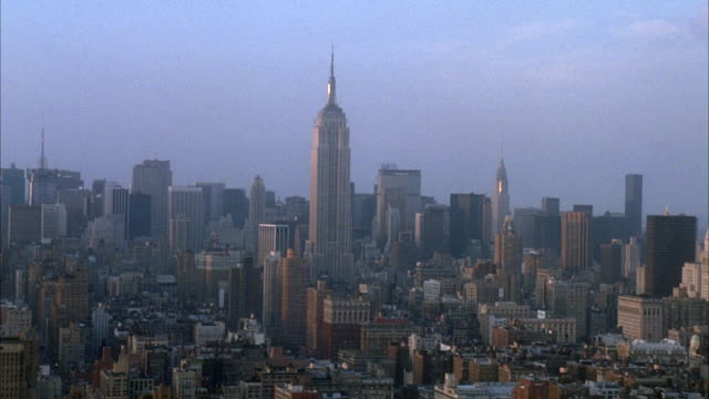 vidéos et rushes de aerial pov moving from right to left of midtown manhattan new york city skyline. see empire state building in center with other skyscrapers in background. - 1980 1989