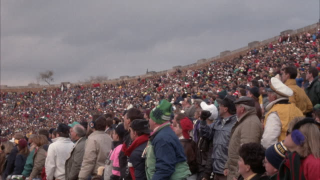 medium angle of crowd of spectators at college football game, could be professional sporting event in stadium. people wear jackets and scarves, probably late autumn or winter. people stand and wait in anticipation. notre dame university. - south bend indiana stock videos & royalty-free footage