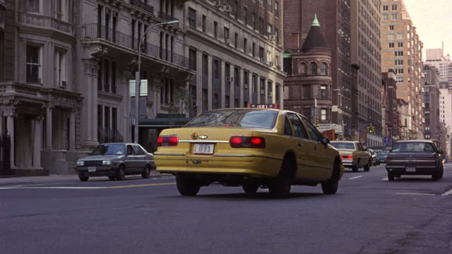 MEDIUM ANGLE OF TRAFFIC ON NEW YORK CITY STREET INTERSECTION. SEE WHITE 1987 BUICK LESABRE CHANGE LANES, DRIVE ON THE WRONG SIDE OF THE YELLOW LINE, TURN RIGHT TO CUT OFF ONCOMING TRAFFIC, AND EXIT SPEEDING TO BACKGROUND.