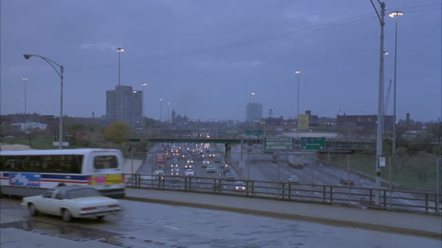 stockvideo's en b-roll-footage met medium angle of chicago bus passing right to left on expressway overpass. see traffic on eight lane expressway and office building in background. overcast sky. freeways. highways. - 1992